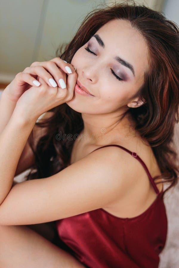 Mujer joven asiática sonriente sensual feliz de la muchacha con el pelo rizado largo oscuro en la ropa interior roja que se sient fotografía de archivo libre de regalías