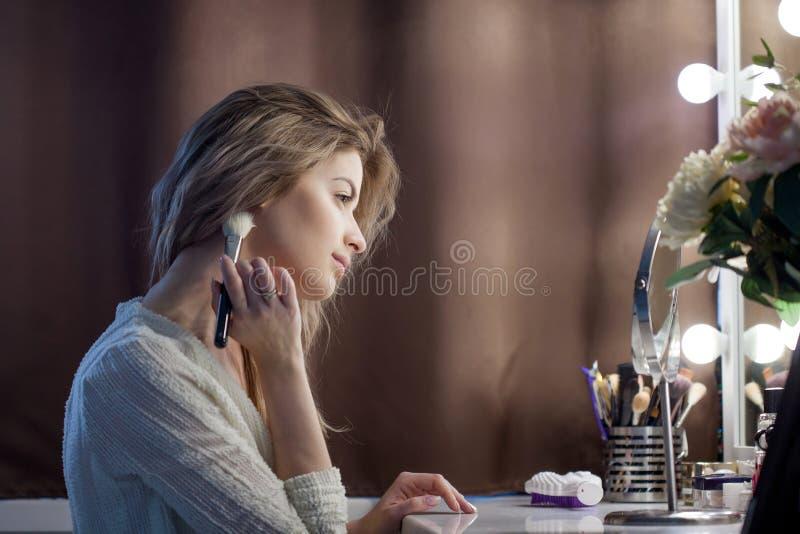Mujer joven asombrosa que hace su maquillaje delante del espejo Retrato de la muchacha hermosa cerca de la tabla cosmética foto de archivo libre de regalías