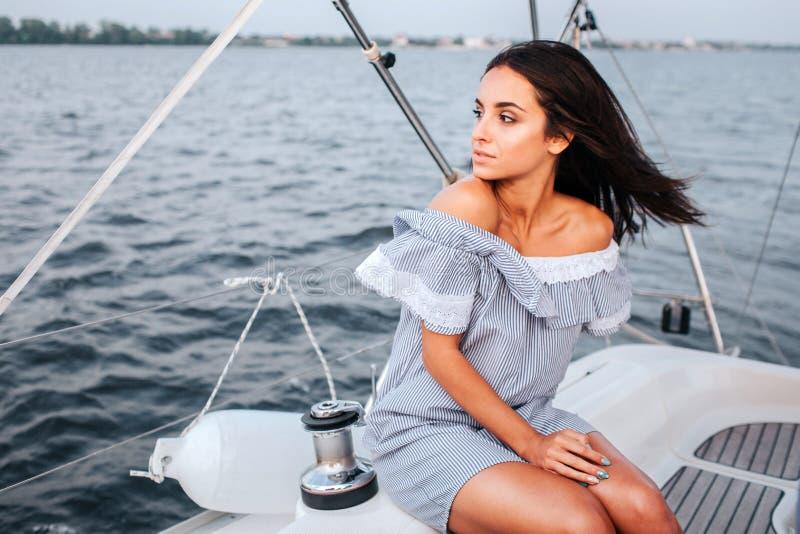 Mujer joven asombrosa y hermosa que se sienta a bordo del yate y de la mirada a la izquierda Ella es tranquila y pacífica La muje imagenes de archivo