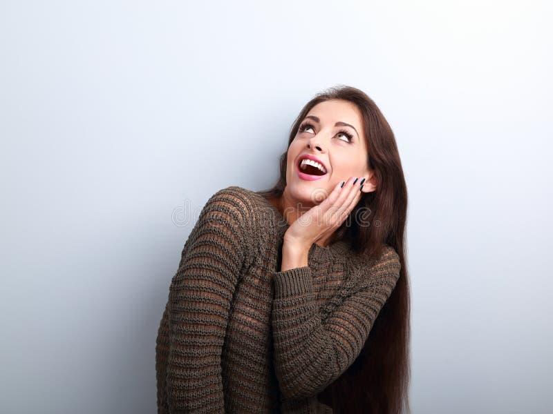 Mujer joven asombrosamente emocionada con la boca abierta que mira para arriba imagenes de archivo
