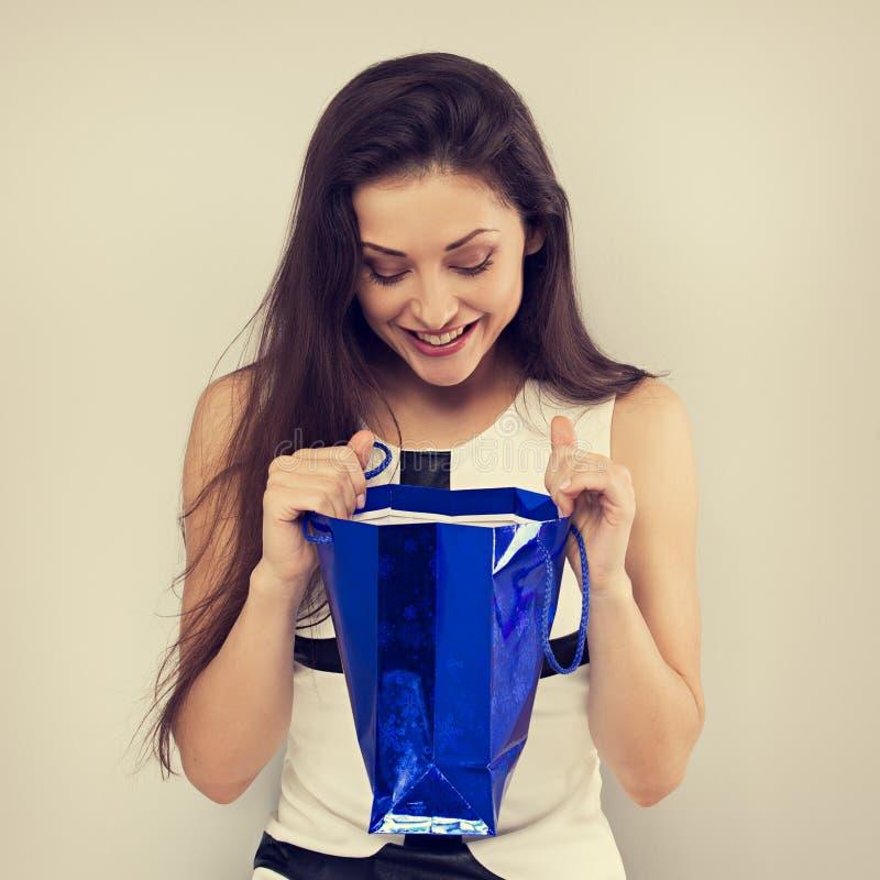 Mujer joven asombrosamente emocionada que mira en bolso azul del regalo con la sonrisa en fondo azul Buenas fiestas foto de archivo libre de regalías