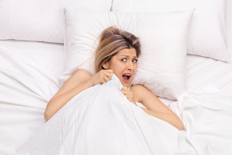 Mujer joven asustada que miente en cama imagen de archivo