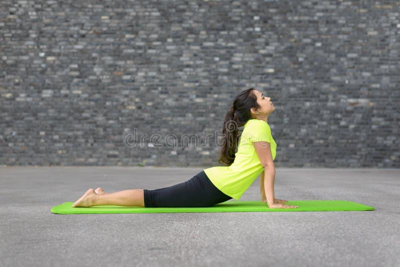 Mujer joven atlética apta que hace ejercicios de la yoga imágenes de archivo libres de regalías