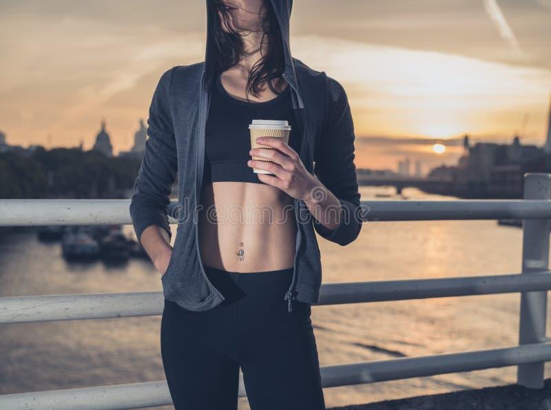 Mujer joven atlética con la taza en Londres en la salida del sol fotografía de archivo libre de regalías