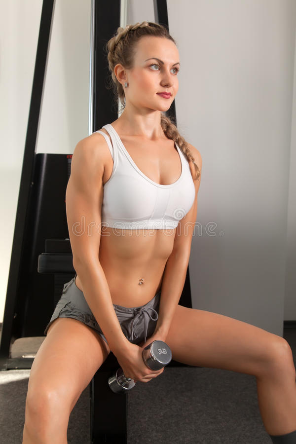 Mujer joven atlética con pesa de gimnasia imagen de archivo