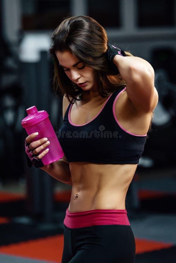 Mujer joven atlética después del entrenamiento duro en el gimnasio La muchacha de la aptitud sostiene la coctelera con la nutrici imágenes de archivo libres de regalías