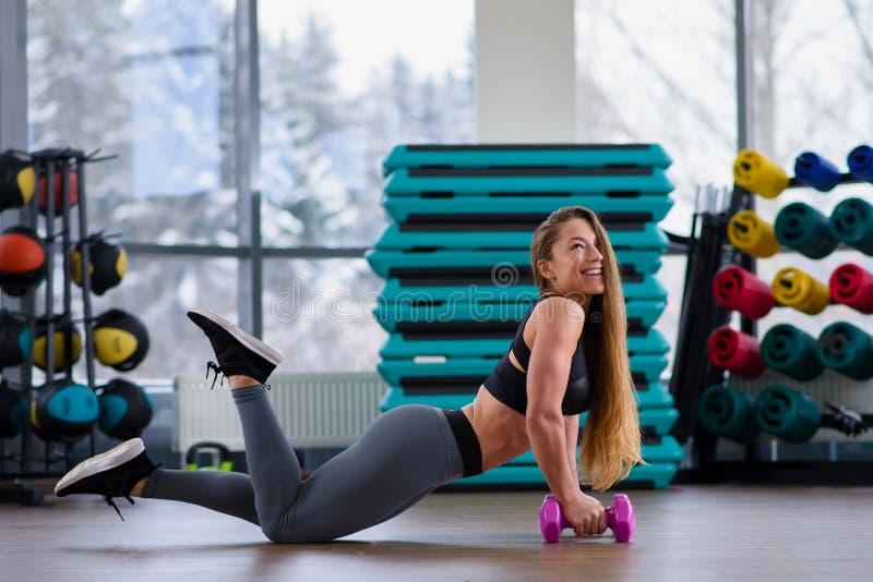 Mujer joven atlética durante entrenamiento en la clase de la aptitud Muchacha hermosa con el cuerpo perfecto y la forma que prese fotografía de archivo