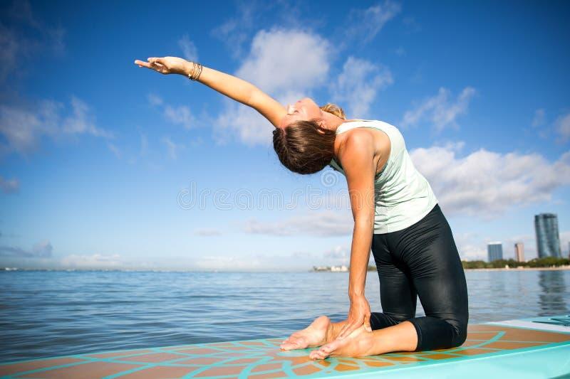 Mujer joven atlética en actitud de la curva de la parte posterior de la práctica de la yoga del SORBO en Ala foto de archivo