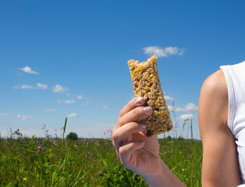 Mujer joven atlética que come la barra de caramelo del cereal afuera Concepto sano de la forma de vida fotografía de archivo