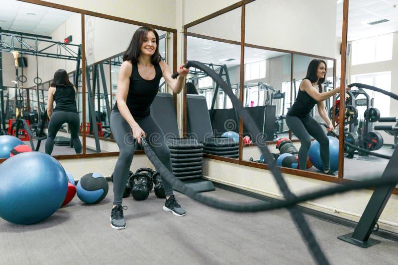 Mujer joven atlética que ejercita en el gimnasio usando cuerdas de la batalla Aptitud, deporte, entrenamiento, gente, concepto sa fotografía de archivo
