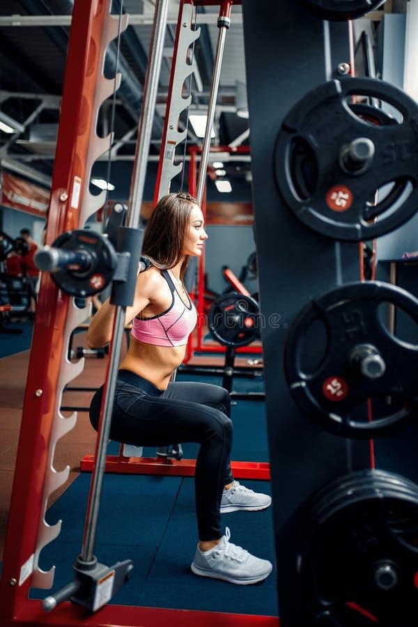 Mujer joven atlética que hace ejercicio del deadlift en la máquina del forjador imágenes de archivo libres de regalías