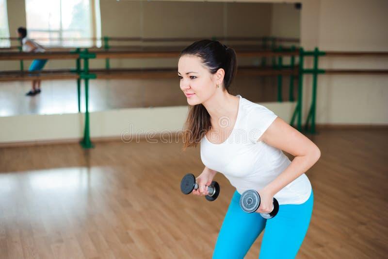 Mujer joven atlética que hace ejercicios con pesas de gimnasia en el gimnasio fotos de archivo libres de regalías