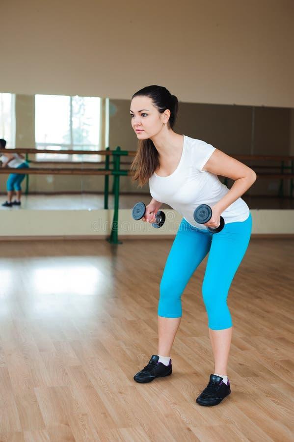 Mujer joven atlética que hace ejercicios con pesas de gimnasia en el gimnasio fotos de archivo