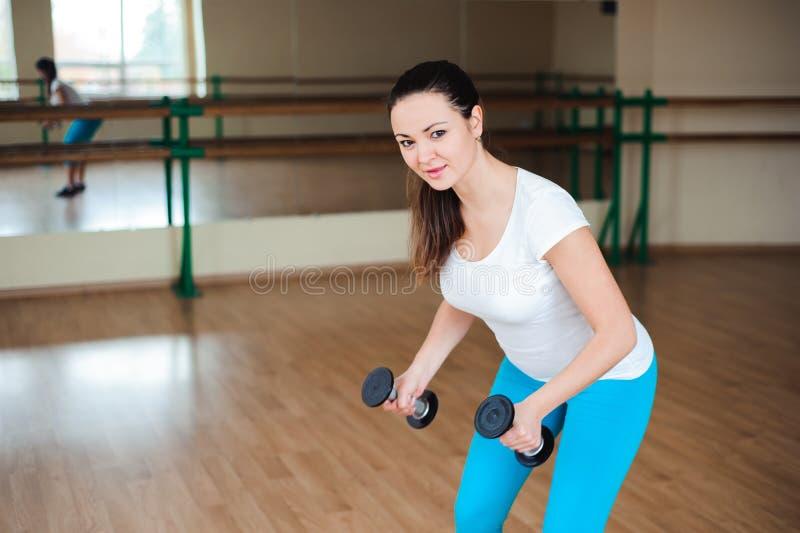 Mujer joven atlética que hace ejercicios con pesas de gimnasia en el gimnasio imagen de archivo libre de regalías