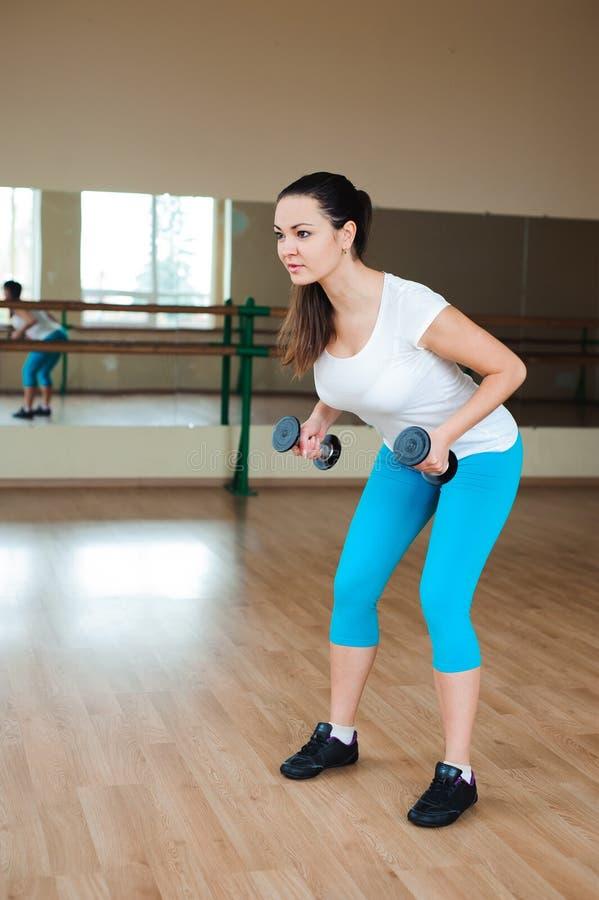 Mujer joven atlética que hace ejercicios con pesas de gimnasia en el gimnasio fotografía de archivo