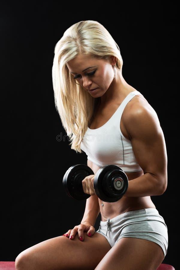 Mujer joven atlética que hace un entrenamiento de la aptitud con pesa de gimnasia fotos de archivo libres de regalías