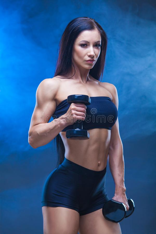 Mujer joven atlética que hace un entrenamiento de la aptitud con pesas de gimnasia en fondo negro del estudio Alrededor de las cu fotografía de archivo