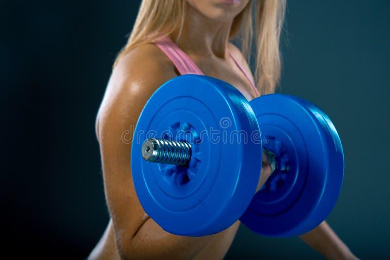 Mujer joven atlética que hace un entrenamiento de la aptitud con pesas de gimnasia en fondo oscuro del estudio imagen de archivo