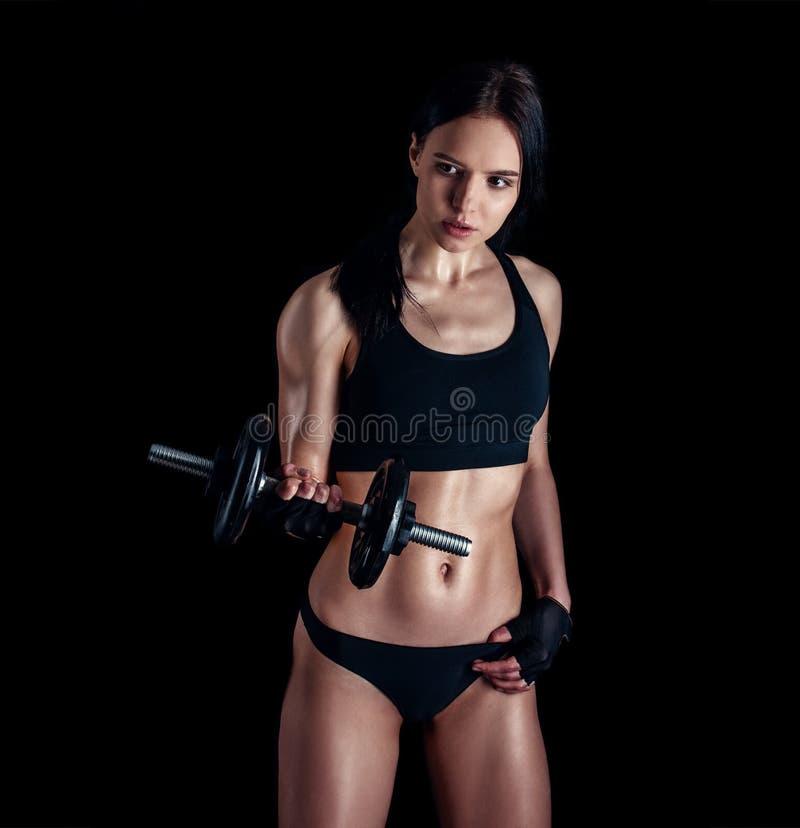 Mujer joven atlética que hace un entrenamiento de la aptitud contra fondo negro La muchacha atractiva de la aptitud que bombea pa imagen de archivo