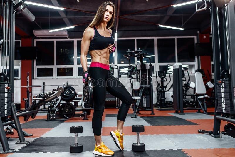 Mujer joven atlética que muestra los músculos después de entrenamiento en gimnasio imagenes de archivo