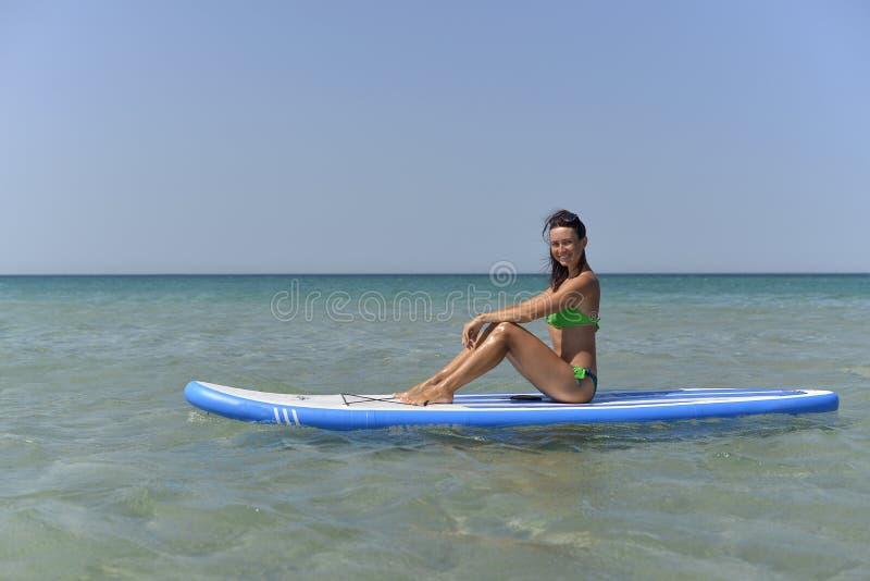 Mujer joven atlética que se sienta en un tablero para SAP que practica surf en el mar en verano foto de archivo