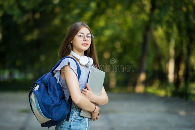 Mujer joven atractiva alegre con la mochila y los cuadernos que se colocan y que sonríen en parque imagenes de archivo