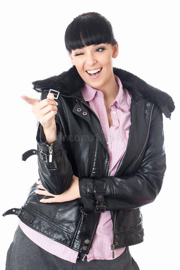 Mujer joven atractiva alegre coqueta feliz que señala y que guiña imagen de archivo libre de regalías