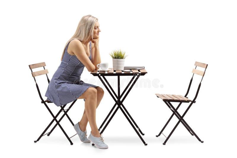 Mujer joven atractiva asentada en una mesa de centro foto de archivo