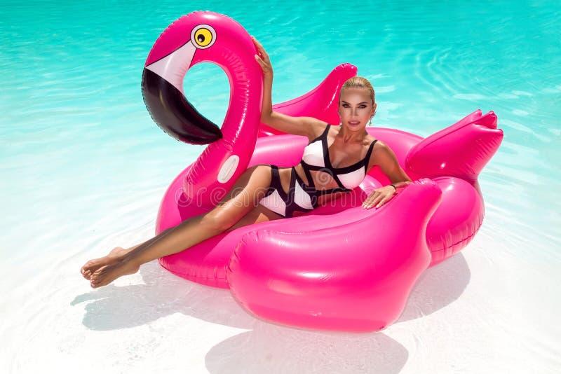 Mujer joven atractiva, asombrosa hermosa en una piscina que se sienta en un llameante rosado inflable y que ríe, cuerpo bronceado imagenes de archivo
