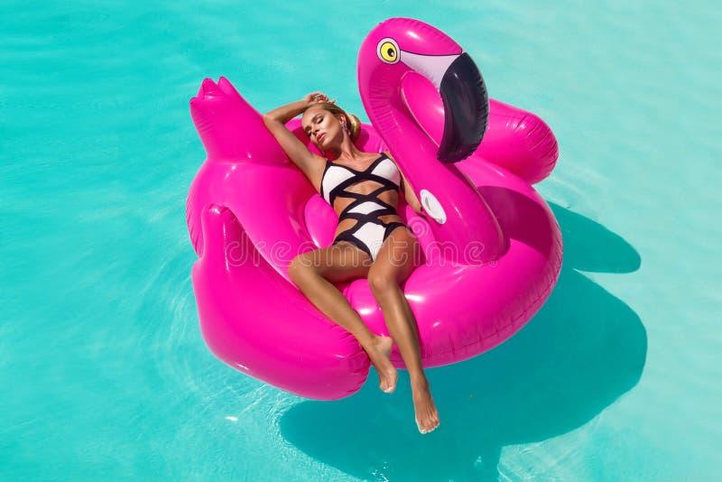 Mujer joven atractiva, asombrosa hermosa en una piscina que se sienta en un llameante rosado inflable y que ríe, cuerpo bronceado imagen de archivo