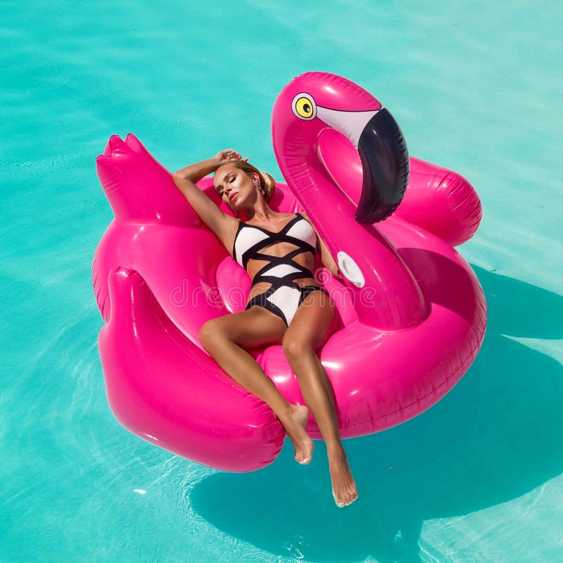 Mujer joven atractiva, asombrosa hermosa en una piscina que se sienta en un llameante rosado inflable y que ríe, cuerpo bronceado fotos de archivo
