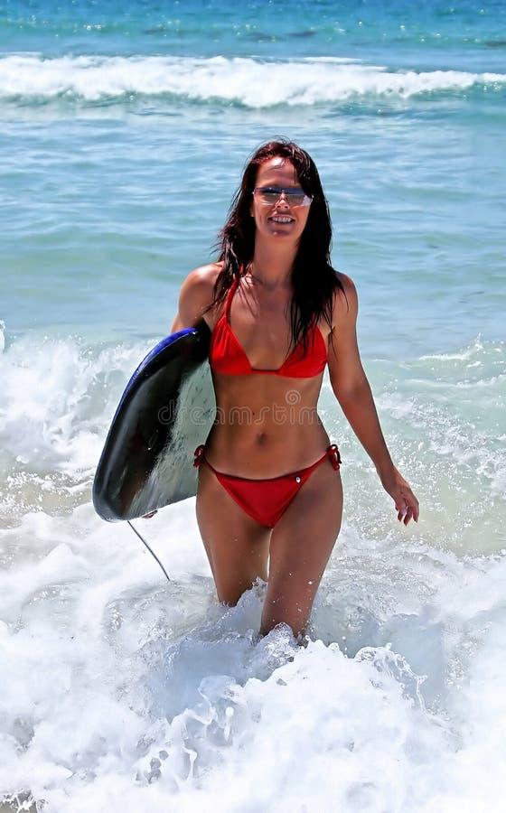 Mujer joven atractiva atractiva en bikiní rojo que recorre adentro del mar azul en la playa asoleada con la tarjeta de la carrocer imagen de archivo libre de regalías