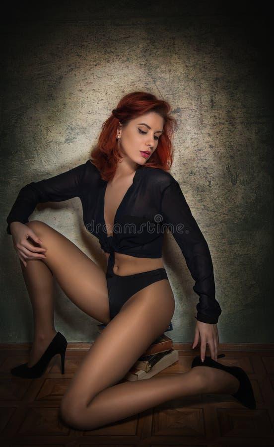 Mujer joven atractiva atractiva en camisa negra y las bragas que se sientan en una pila de libros en el piso Pelirrojo sensual co imagenes de archivo
