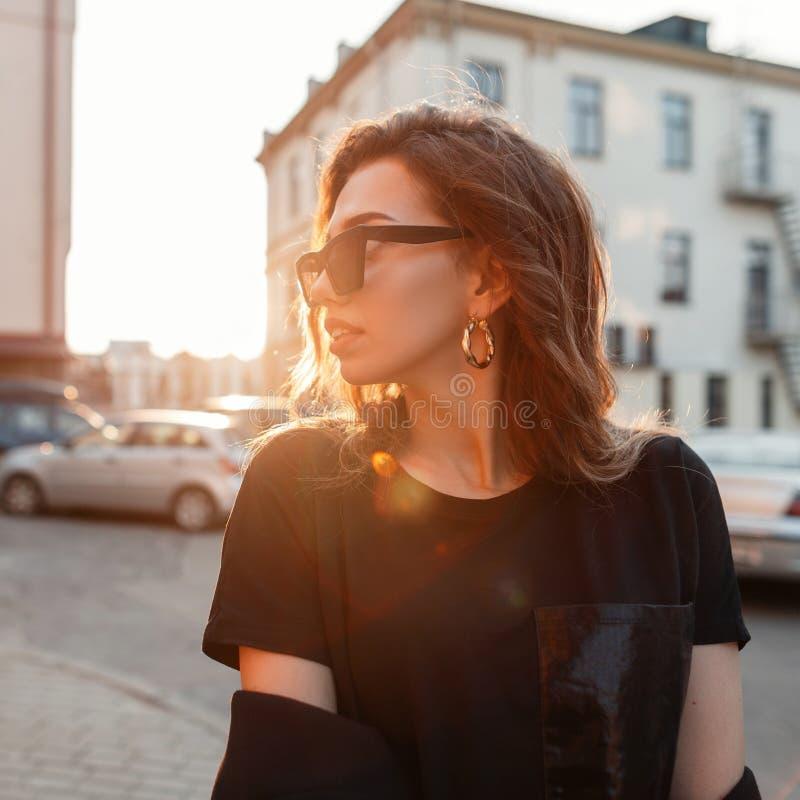 Mujer joven atractiva bonita elegante del inconformista en gafas de sol oscuras de moda en una camiseta negra elegante que presen foto de archivo