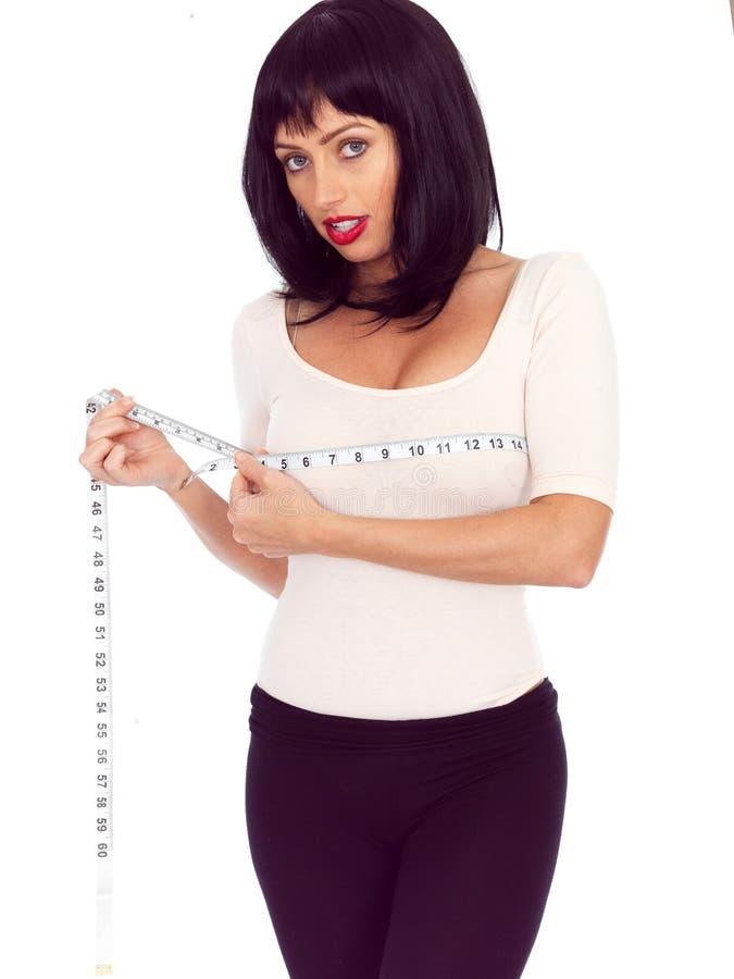 Mujer joven atractiva cabelluda oscura que mide su busto con una cinta métrica fotografía de archivo