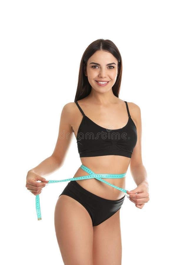 Mujer joven atractiva con el cuerpo delgado que mide su cintura fotos de archivo