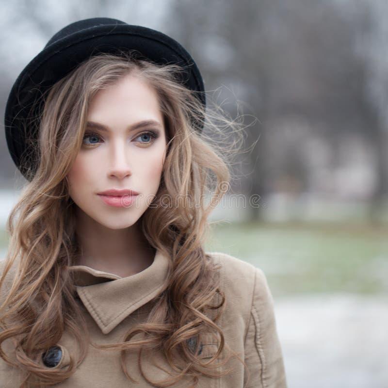 Mujer joven atractiva con el peinado ondulado al aire libre fotos de archivo