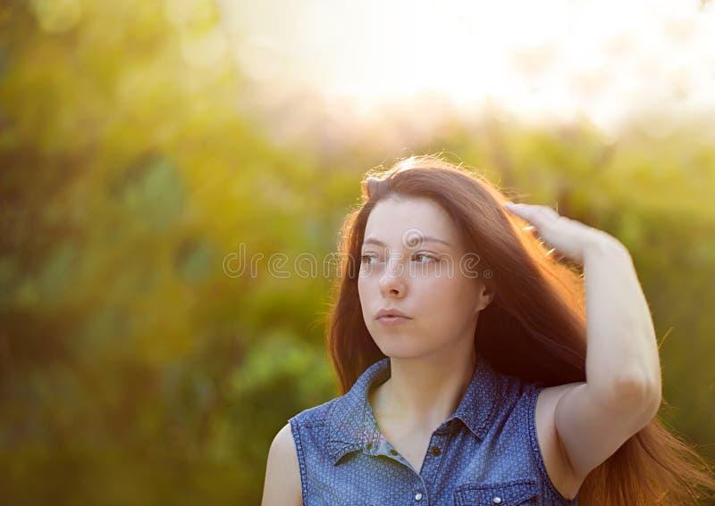 Mujer joven atractiva con el pelo marrón largo que disfruta del hertime adentro fotos de archivo libres de regalías
