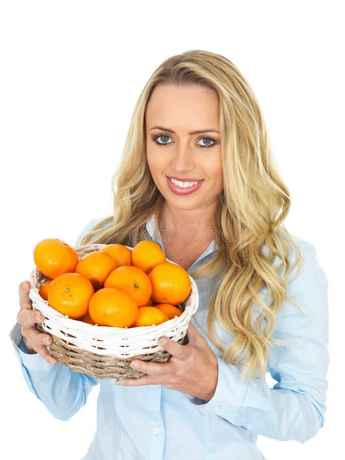 Mujer joven atractiva con el pelo rubio que sostiene una cesta de mandarinas imagen de archivo libre de regalías