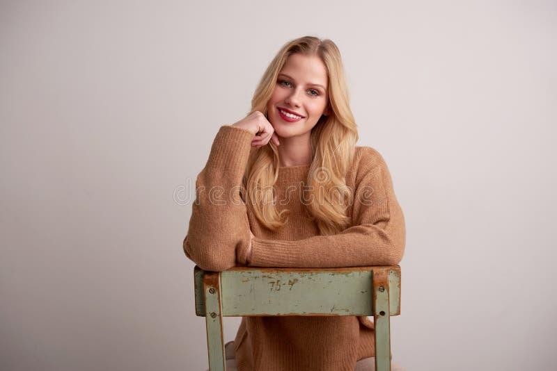 Mujer joven atractiva con el pelo rubio y la barra de labios roja que se sientan en el fondo fotografía de archivo libre de regalías