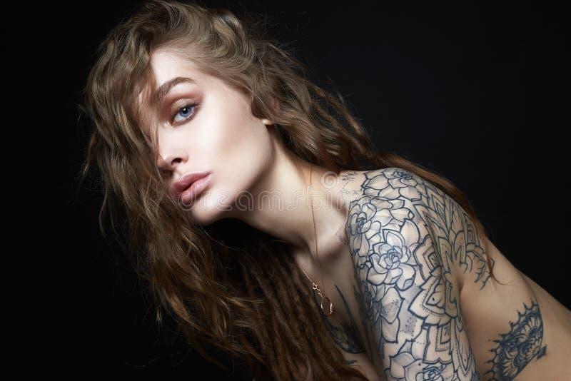 Mujer joven atractiva con el tatuaje fotos de archivo