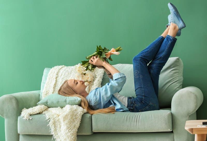 Mujer joven atractiva con las flores hermosas que mienten en el sofá en casa imagen de archivo libre de regalías