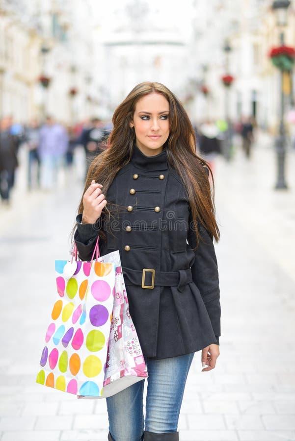 Mujer joven atractiva con los panieres en una calle comercial imagenes de archivo
