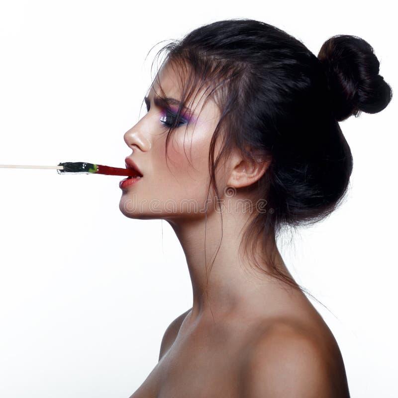 Mujer joven atractiva con los pelos apretados, con los hombros desnudos, sosteniendo en boca una piruleta, aislada en un fondo bl foto de archivo