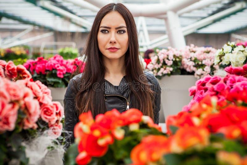 Mujer joven atractiva con los pelos hermosos largos que presentan en el invernadero de la flor del parque de Keukenhof imagenes de archivo