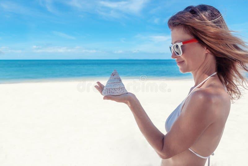 Mujer joven atractiva con un bikini blanco contra un t hermoso imagen de archivo