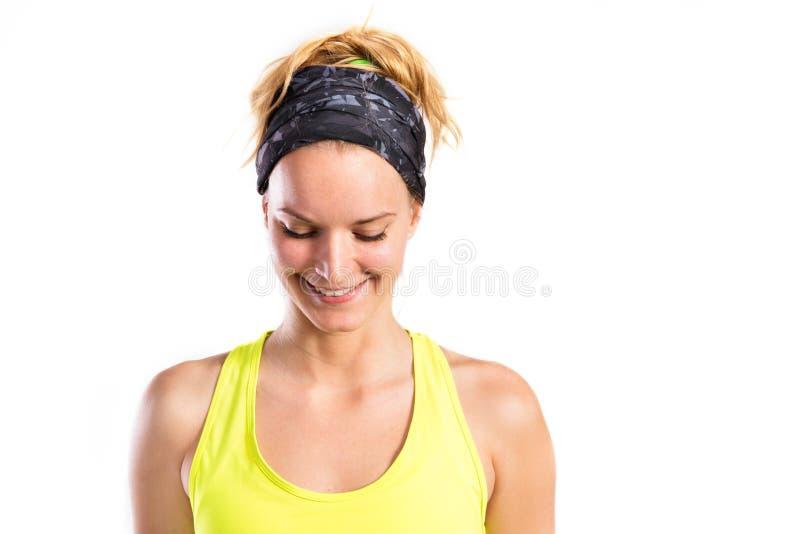Mujer joven atractiva de la aptitud en top sin mangas amarillo Tiro del estudio imagen de archivo