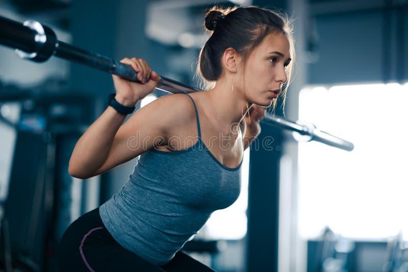 Mujer joven atractiva de los deportes que hace posiciones en cuclillas con el Barbell en el gimnasio Aptitud y forma de vida sana fotografía de archivo