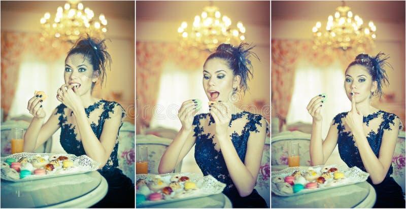 Mujer joven atractiva de moda en vestido negro que come los macarrones en restaurante Morenita hermosa que sostiene las galletas fotos de archivo