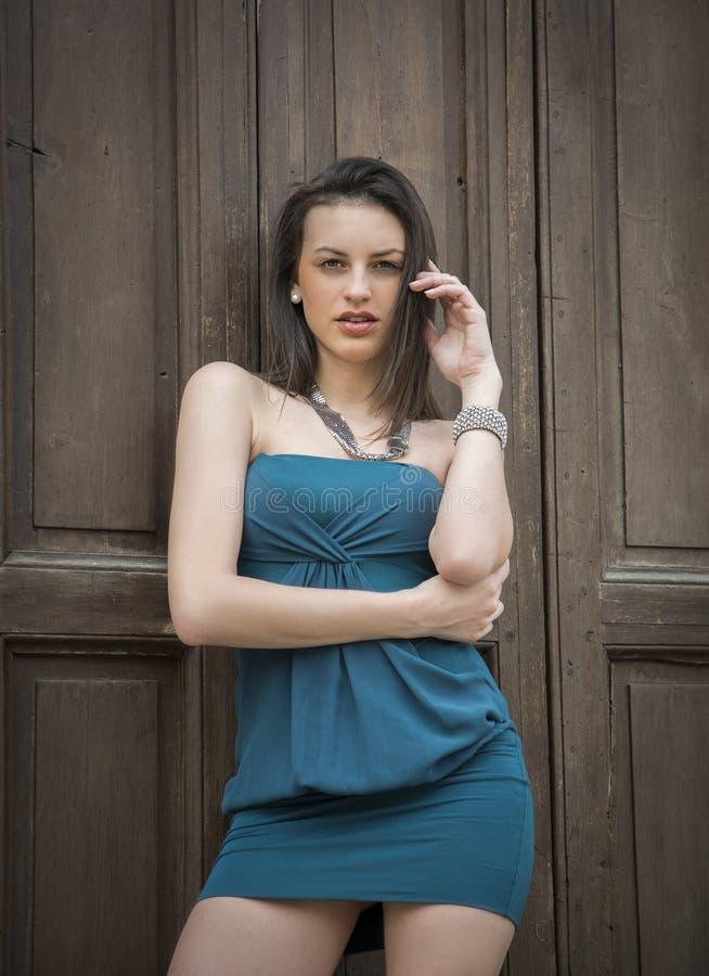 Mujer joven atractiva elegante contra la puerta de madera imagen de archivo